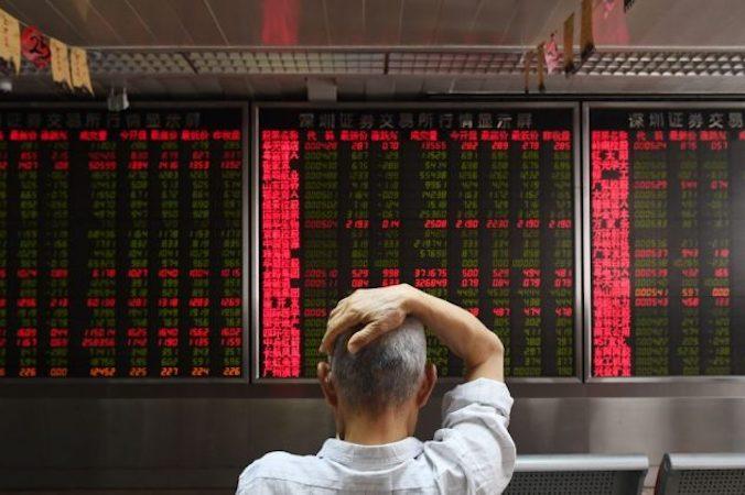 Mężczyzna kontroluje ruchy cenowe wfirmie inwestycyjnej wPekinie wdniu 4.07.2018 r. (Greg Baker/AFP/Getty Images)
