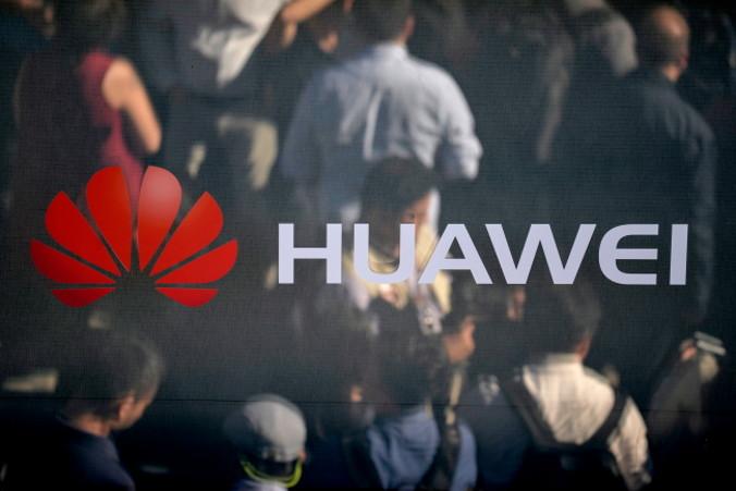 Zwiedzający odbijają się wlustrze zlogo firmy Huawei, Monachium, Niemcy, 16.10.2017 r. Ponownie wydane 11.01.2019 r. (PHILIPP GUELLAND/PAP/EPA)